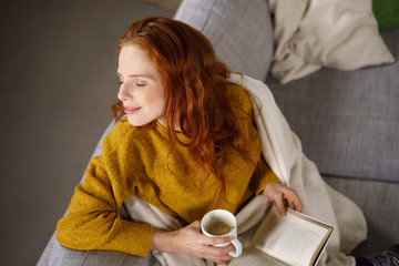 verträumte frau mit einem buch und einer tasse kaffee auf dem sofa