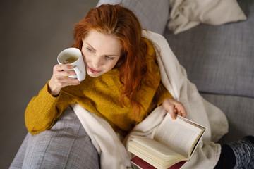 attraktive frau mit einer tasse kaffee und einem buch auf dem sofa
