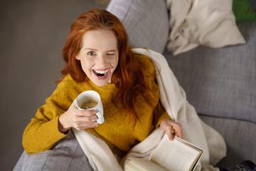 frau entspannt auf dem sofa und zwinkert mit einem auge