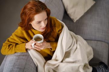 frau kuschelt sich in eine decke und genießt eine tasse kaffee