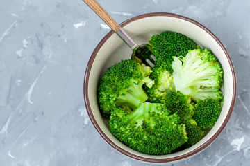 Boiled broccoli in a bowl on a concrete background.