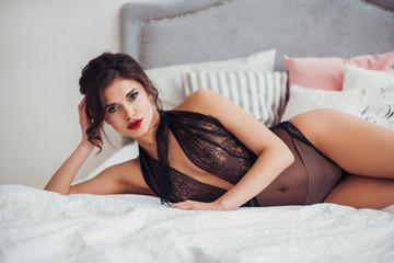 Beautiful sexy woman wearing seductive black lingerie posing in bedroom