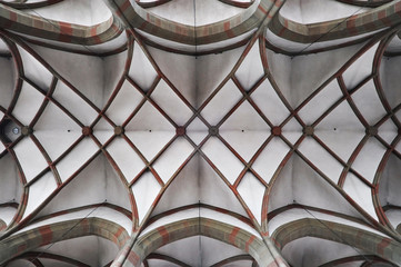 Arched ceiling of gothic church. Stone frame and white filling. Symmetrical form, look up.