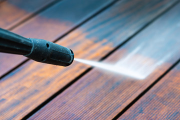 cleaning terrace with a power washer - high water pressure cleaner on wooden terrace surface - focus on the end of washer - shallow depth of field