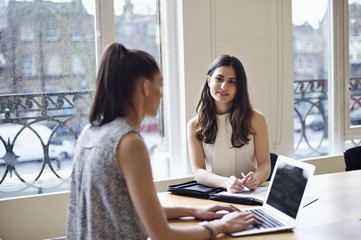 Young caucasian businesswoman in office with mixed race colleague