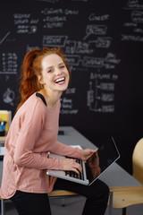 lachende junge frau arbeitet am laptop