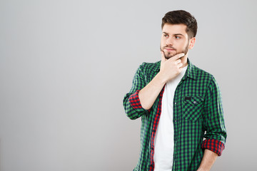 Thoughtful man in green and red checked t-shirt