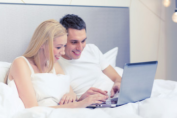 smiling couple in bed with laptop computer