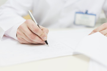 male doctor sitting table writing