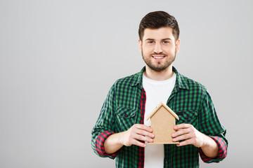 Man holding little wooden house