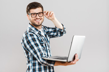Man holding opened laptop and touching glasses