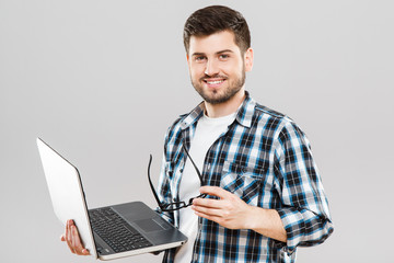 Man holding laptop and glasses