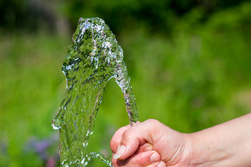 Fountain flowing from hands, on green background
