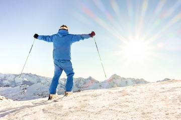 Young skier at the top of mountain raising arms