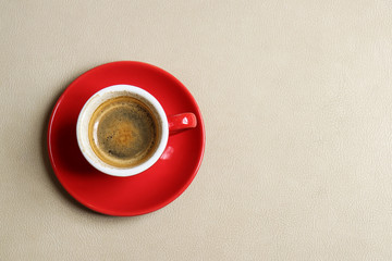 Red cup of Espresso on light brown seat leather.