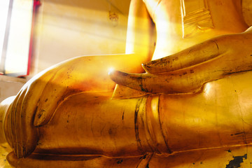 Selective focus hand of Buddha statue near window with sunday light at Wat Pa Rerai temple in Suphanburi, Thailand.