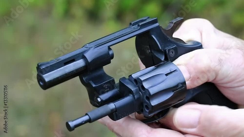 Man holds in hands black revolver with flobert cartridges