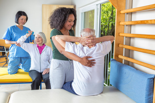 African nurse helping elder man with with physical exercises in