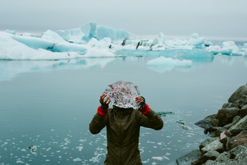 Woman looking through ice by sea