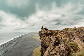 Man sitting on cliff and looking at sea