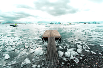 Wooden jetty and boats on icy sea