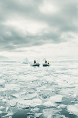 Boats and crew on icy sea