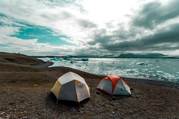 Two tents by shoreline