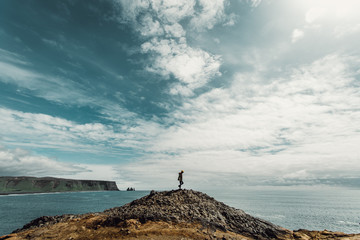 Person stood on rock formation by sea