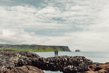 Couple standing on natural arch by sea