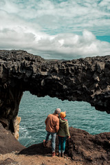 Couple looking through natural arch at sea