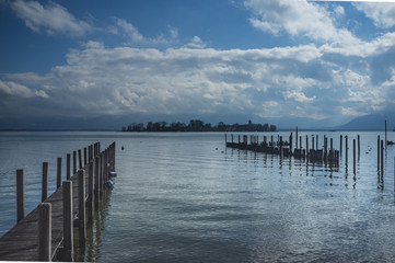 Jetty at the lake Chiemsee with blue sky and clouds, Chiemgau, Bavaria