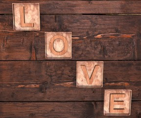 3D Wooden letters forming word LOVE written on wooden background. St. Valentine's Day.