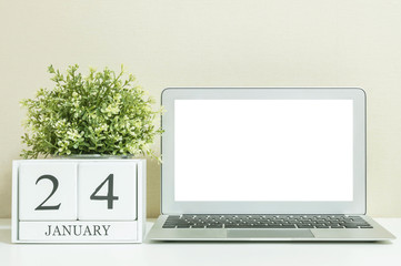 White wooden calendar with black 24 january word with white blank space at center of computer notebook on white wood desk and cream wallpaper textured background , selective focus at the calendar