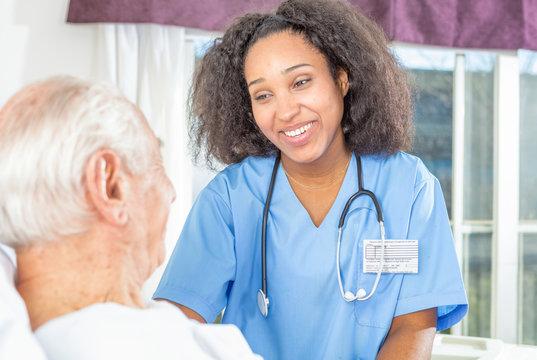 African nurse smiling to elder male patient