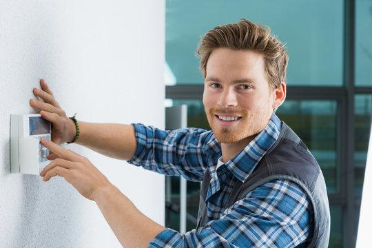 handsome young electrician repairing intercom