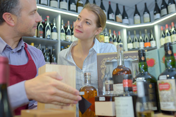 Sales assistant with customer in liquor store