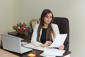 beautiful smiling business woman working at her office desk with documents.