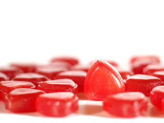 red hard candies closeup on white background, shallow depth of field, selective focus, copy space
