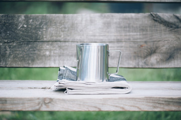 Frothing milk pitcher on the cloth napkin on the wooden background