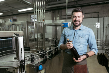 Smiling man holding a bottle of alcohol at brewing factory