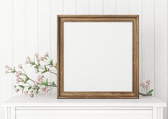 Square interior mock up with empty wooden frame and blooming twig on wooden wall background. 3D rendering.