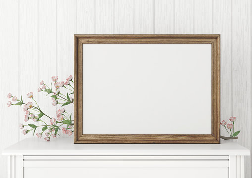 Horizontal interior mock up with empty wooden frame and blooming twig on wooden wall background. 3D rendering.
