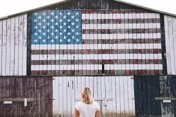 Woman in front of building with American flag