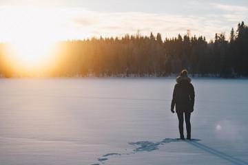 Frau schaut in den Sonnenuntergang im Winter