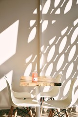Table, chairs and sun reflecting on wall