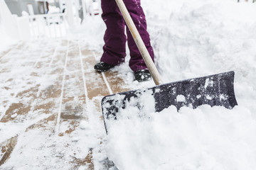 woman shoveling and removing snow outside