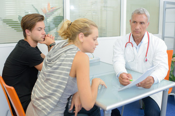 Doctor in consultation with couple