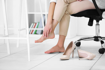 Barefoot woman in office at work