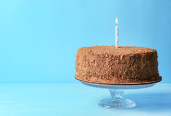 Tasty chocolate cake with candle on blue background