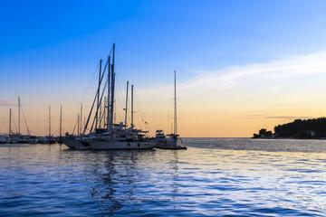 Sailing ships at sea at sunset.